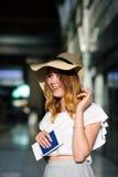 Muchacha bonita en un sombrero de ala ancha con el pasaporte y boletos en una mano Fotos de archivo