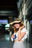 Muchacha bonita en un sombrero de ala ancha con el pasaporte y boletos en una mano Imagenes de archivo