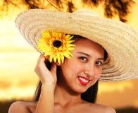 Muchacha bonita en un sombrero en la puesta del sol Imagen de archivo