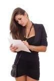 Muchacha bonita en vestido negro con el monedero que anota algo Foto de archivo libre de regalías