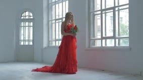 Muchacha bonita en vestido rojo magnífico que camina más allá de almacen de metraje de vídeo