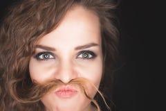 Muchacha bonita enojada que hace el bigote de su pelo Imagen de archivo