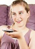 Muchacha bonita feliz con la TV de observación teledirigida Fotos de archivo