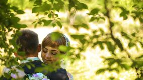 Muchacha bonita feliz de novia y del novio que abraza y que se besa en el bosque almacen de video