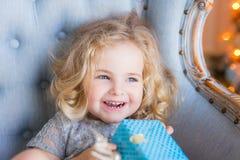Muchacha bonita feliz que sonríe llevando a cabo el regalo de Navidad en manos Imagen de archivo