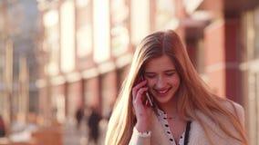 Muchacha bonita hermosa que habla en su teléfono y que ríe mientras que camina abajo de la calle soleada en el centro de ciudad e almacen de video