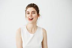 Muchacha bonita joven alegre que sonríe mirando la cámara que muestra la lengua sobre el fondo blanco Foto de archivo libre de regalías