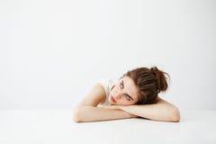 Muchacha bonita joven cansada aburrida con el bollo que piensa soñando la mentira en la tabla sobre el fondo blanco Foto de archivo