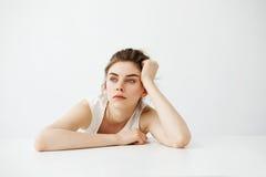 Muchacha bonita joven cansada aburrida con el bollo que piensa soñando sentarse en la tabla sobre el fondo blanco Imagenes de archivo