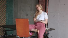 Muchacha bonita joven con el cepillo y paleta que se sienta cerca de imagen del dibujo del caballete Arte, creatividad, afici?n,  almacen de metraje de vídeo