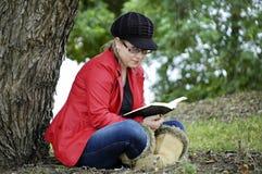 Muchacha bonita joven con el libro de lectura relajante de la expresión fresca en campo Fotos de archivo libres de regalías
