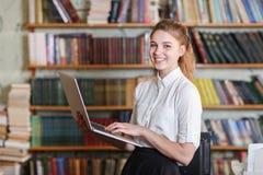 Muchacha bonita joven con el ordenador portátil que presenta en la cámara en la biblioteca Fotografía de archivo