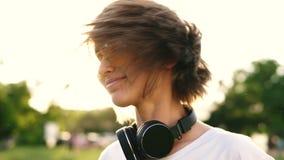 Muchacha bonita joven con el pelo justo corto que sacude su cabeza aislada sobre fondo verde del parque Mujer caucásica en amaril almacen de video