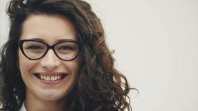 Muchacha bonita joven con el pelo magnífico En un fondo blanco Vestido en sonrisas de los vidrios sinceramente almacen de video