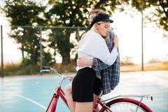 Muchacha bonita joven con el pelo rubio que la cierra soñador ojos mientras que abraza al muchacho en la bicicleta roja en la can Imagen de archivo