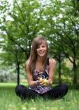 Muchacha bonita joven con las manzanas en la hierba Fotos de archivo