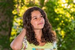 Muchacha bonita joven con un pelo rizado al aire libre Fotos de archivo