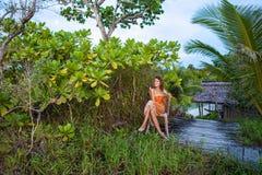 Muchacha bonita joven de la foto que goza de las frutas exóticas en puesta del sol de la casa de la selva Verano al aire libre so Fotografía de archivo