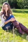 Muchacha bonita joven del adolescente que se sienta en hierba verde Imagenes de archivo