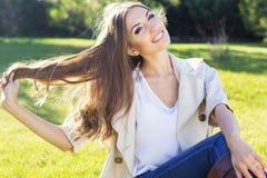 Muchacha bonita joven del adolescente que se sienta en hierba verde Fotos de archivo