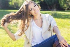 Muchacha bonita joven del adolescente que se sienta en hierba verde Imagen de archivo libre de regalías