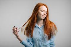 Muchacha bonita joven del pelirrojo con las pecas que miran el pelo conmovedor sonriente de la cámara Imágenes de archivo libres de regalías