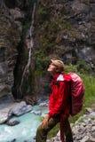Muchacha bonita joven del retrato que lleva las montañas rojas del rastro de la mochila de la chaqueta Opinión de la cascada del  Fotografía de archivo libre de regalías
