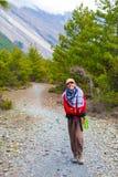 Muchacha bonita joven del retrato que lleva las montañas rojas del rastro de la mochila de la chaqueta Opinión de la trayectoria  Fotografía de archivo