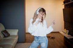 Muchacha bonita joven en auriculares con el teléfono Escuchando la música, el baile y el canto, dentro Fotos de archivo