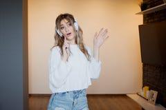 Muchacha bonita joven en auriculares con el teléfono Escuchando la música, el baile y el canto, dentro Fotografía de archivo libre de regalías