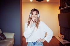 Muchacha bonita joven en auriculares con el teléfono Escuchando la música, el baile y el canto, dentro Imagenes de archivo