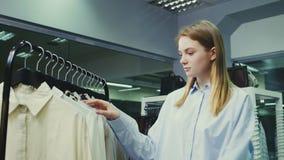 Muchacha bonita joven en el boutique que selecciona la ropa comprar almacen de video
