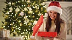Muchacha bonita joven en Santa Hat Opening Christmas Present y sonrisa después de esto La mujer sorprendida de risa mira dentro almacen de metraje de vídeo