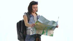 Muchacha bonita joven en vacaciones con el mapa y backpacklooking in camera con la expresión divertida Imagen de archivo libre de regalías