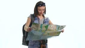 Muchacha bonita joven en vacaciones con el mapa y backpacklooking in camera con la expresión divertida Imagen de archivo