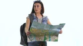 Muchacha bonita joven en vacaciones con el mapa y backpacklooking in camera con la expresión divertida Foto de archivo libre de regalías