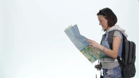 Muchacha bonita joven en vacaciones con el mapa y backpacklooking in camera con la expresión divertida Fotos de archivo libres de regalías