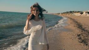 Muchacha bonita joven que camina cerca de la playa y metrajes