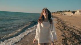 Muchacha bonita joven que camina cerca de la playa y almacen de video