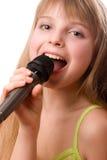 Muchacha bonita joven que canta en el micrófono Imagen de archivo libre de regalías