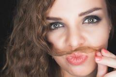 Muchacha bonita joven que hace el bigote de su pelo Imagenes de archivo
