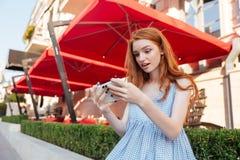 Muchacha bonita joven que juega a juegos en el teléfono móvil Fotos de archivo libres de regalías
