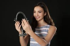 Muchacha bonita joven que mira en espejo Imagen de archivo libre de regalías