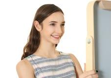 Muchacha bonita joven que mira en espejo Fotos de archivo