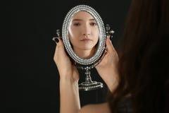 Muchacha bonita joven que mira en espejo Fotografía de archivo libre de regalías