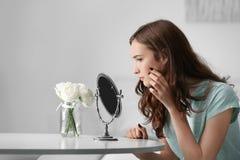 Muchacha bonita joven que mira en espejo Imagen de archivo