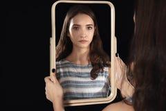 Muchacha bonita joven que mira en espejo Fotografía de archivo