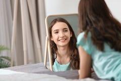 Muchacha bonita joven que mira en espejo Imagenes de archivo