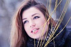 Muchacha bonita joven que muerde una rama del sauce en el bosque Imagen de archivo