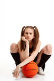 Muchacha bonita joven que presenta con baloncesto sobre el fondo blanco Fotos de archivo